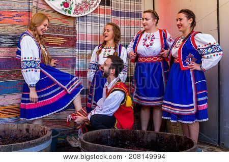 Bobovysche Ukraine - 2017 October 7: The young man wipes the feet of the girls after squeezing out the grapes in barrels during the ethnic festival Bobovishchenske Grono.