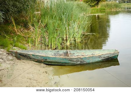 old wooden boat on the shore of a small pond, river or lake in the afternoon.