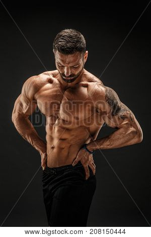 Very brawny guy bodybuilder posing. Beautiful sporty guy male power. Fitness muscled man.