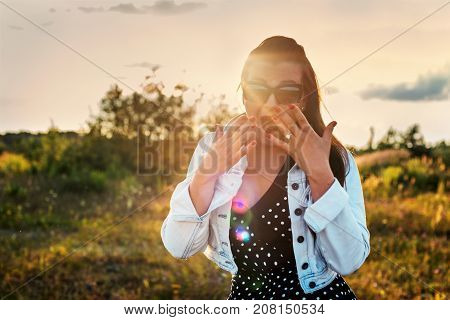 pin up girl is surprised with an open mouth in the rays of the sunset
