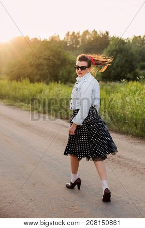 pin up girl goes along the road in the rays of sunset
