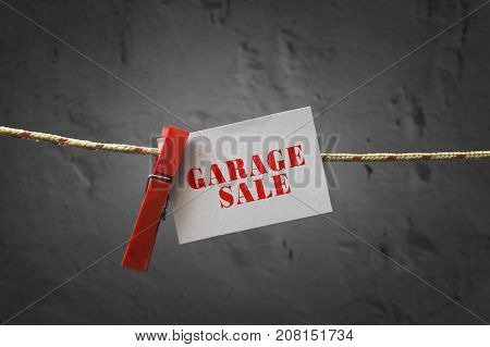 Garage sale card attached to a rope with clothes pins on dark background.