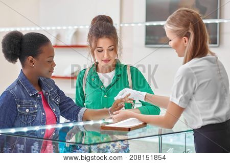 Shot of two happy young women looking at selection of jewellery on the display at the jewelry store.
