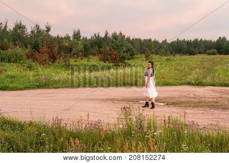 a young woman cowgirl walking along the road at sunset in the evening