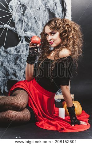 Halloween witch girl sitting on the floor with black wall and spider web on background. Holding pomegranate. Candle and pumpkin in frame