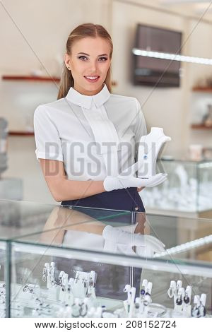 Vertial portrait of a beautiful young woman jewellery store clerk at work.