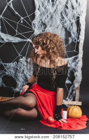 Halloween witch girl sitting on the floor with black wall and spider web on background. Looking down. Candle and pumpkin in frame