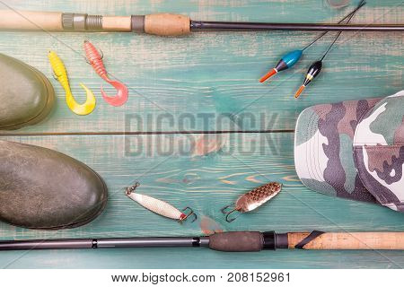 Fishing theme. Frame from fishing rods with fishing tackles, rubber boots, camouflage cap and fishing buoy on green wooden background