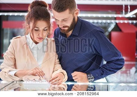 Lovely young couple buying engagement rings at the jewelry store looking at selection of items on a display.