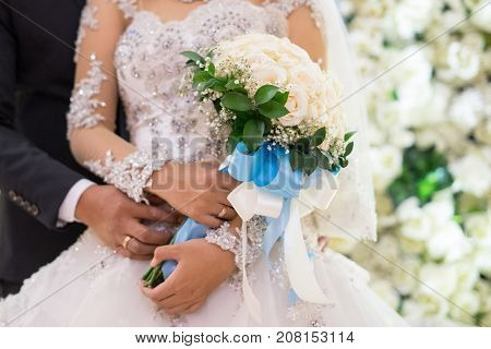 Close up of newly wedding couple holding hand bouquet to show off their wedding rings