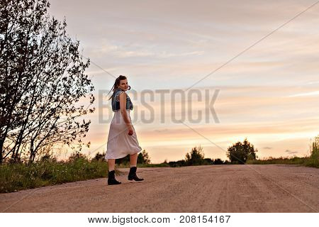 young gypsy woman walking down the road in sunset