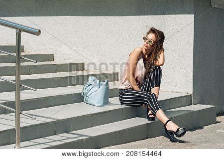 A beautiful woman, the model wears stylish clothes, beige knitwear and black breeches in a white stripe. Women's fashion. Urban lifestyle