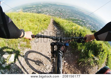 View from the first person rider riding downhill on a narrow mountain trail with a high mountain in the background of the city in the distance in sunny weather in summer.