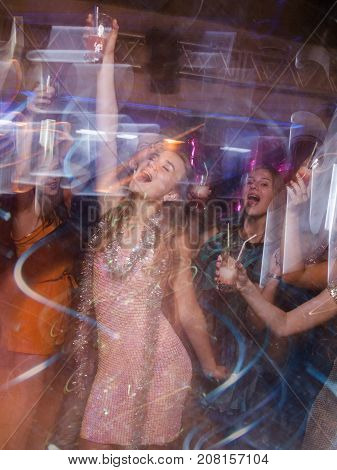 Happy New Year party in blurred motion. Joyful lady at Christmas discotheque, modern youth life, active company with drinks in night club