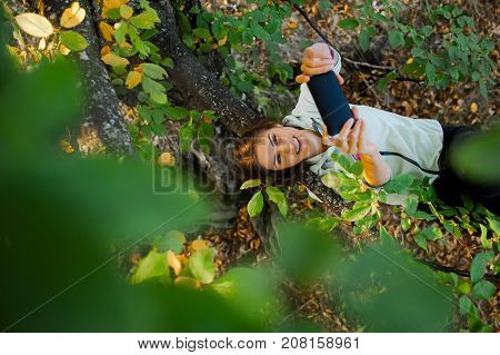 Young woman climbed in a tree lying on a branch taking a selfportrait with a mobile phone at sunset in autumn season.