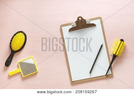 Flat lay of hair comb crest brushes with handle for all types, pocket mirror and folder tablet with pencil, isolated on pink copy space background. Minimalistic feminine flat lay for bloggers, designers, sites.