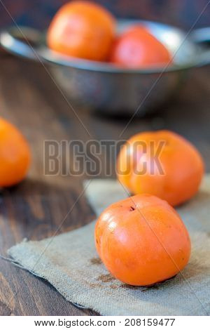 Group of persimmons on wooden table and piece of fabric