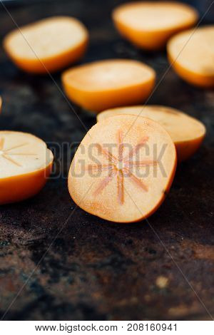 Halves of persimmon fruit on black metal surface