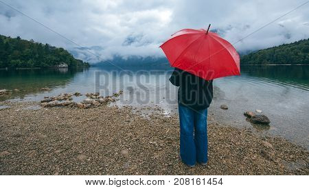 Woman with red umbrella contemplates on rain in front of a lake. Sad and lonely female person looking into distance.