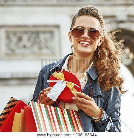 Stylish Christmas in Paris. Portrait of happy elegant woman in trench coat with shopping bags and Christmas present near Arc de Triomphe in Paris France