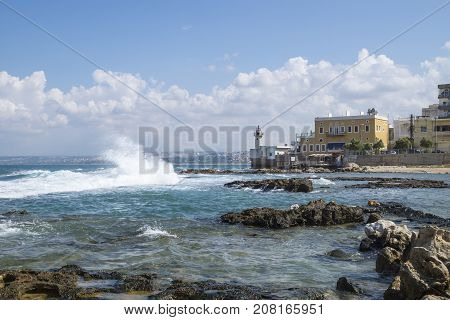 Waves at the seacoast with old lighthouse with blue sky and tiny clouds in Tyre, Sour, Lebanon