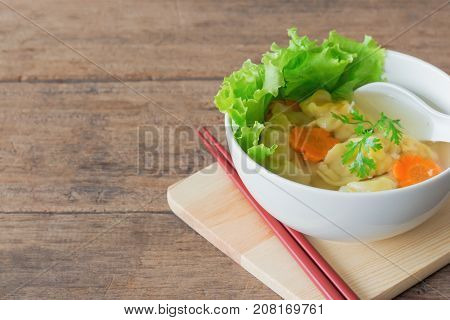 Homemade minced pork and shrimp wonton soup or dumpling soup in white bowl on wood table with copy space. Delicious wonton in clear soup for breakfast or lunch or dinner. Dumpling soup is popular Chinese food. Dumpling soup background.
