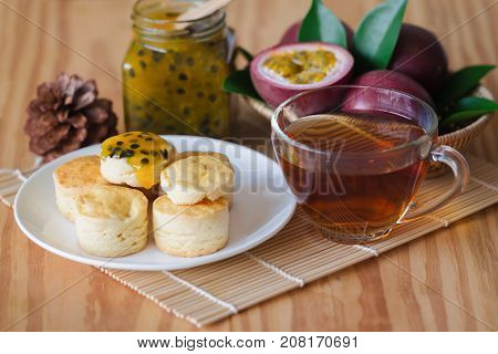 Homemade plain scones serve with passion fruit jam and tea. Scones is traditional English pastry for afternoon tea or coffee break. Delicious scones and passion fruit jam with tea ready to served. Scone and jam ready to served with tea.