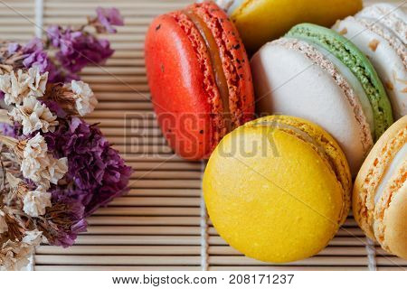 Colorful French macaron or Italian macaron on bamboo mat. Macaron is French popular dessert for served with tea or coffee. Close up view macro concept. Macarons background or wallpaper. Pastel color macaron in macro concept.