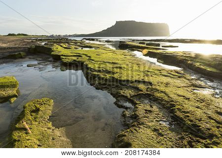 Sunrise at the coast of Seongsan-ri with mossy stones with view to Ilchulbong volcano, Jeju Island, South Korea