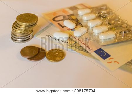 White Tabletts with euros banknotes and coins. Concept Pharmaceutical business cost of health medecine. Scattered pills.