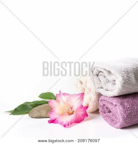 Spa setting of towel pink flower isolated on white background with copy space. Square image.