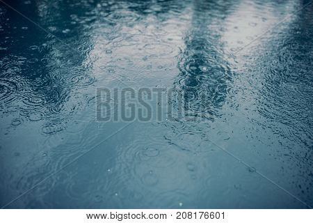 Water surface during rain. Rain drops are falling into the water.