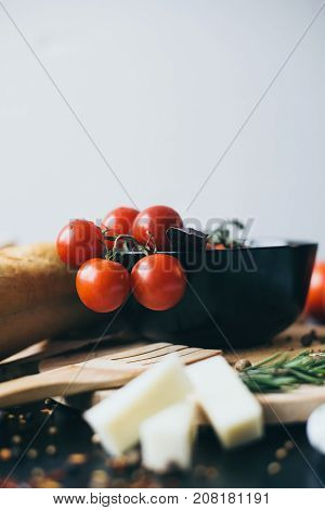 Tasty fresh tomatoes in a stylis black dish with delicious bread lying on wooden cutting board ready for cooking and making amazing meal for lunch or dinner. stylish shot