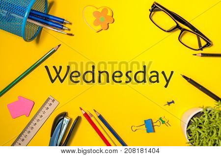 Wednesday. Office supplies or student outfit on yellow table. Business creative consept, top view.