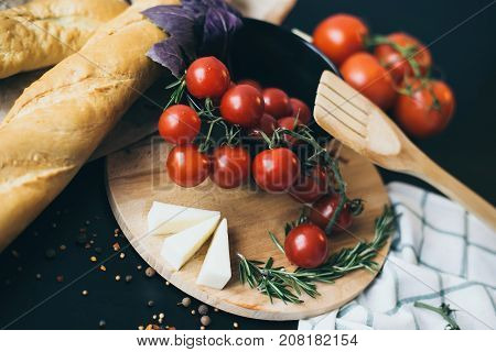 Tasty fresh tomatoes with delicious bread lying on wooden cutting board ready for cooking and making amazing meal for lunch or dinner. Perfect