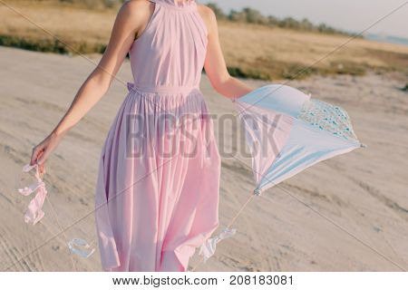 a girl in pink dress launches kite