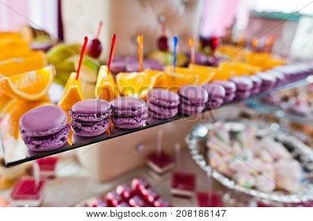 Close-up Photo Of Purple Macaroons And Orange Slices On The Wedding Banquet.
