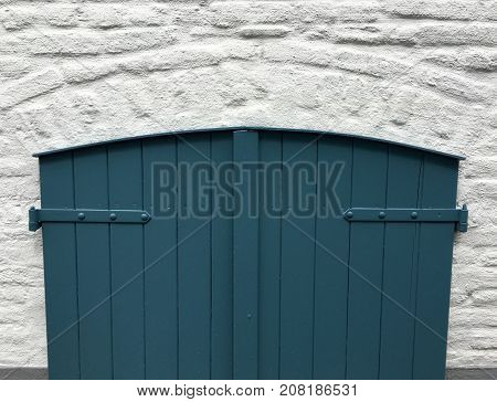 Old wooden door of a basement with blue paint, background