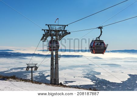 Gondola lift. Cabin of ski-lift in the ski resort in the early morning at dawn with mountain peak in the distance. Winter snowboard and skiing concept.