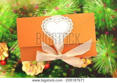Orange gift envelope tied with a pink ribbon on the background of Christmas tree with cones
