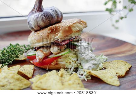 Creatively styled beef burger with rustic home-made French chips or crisps shot against light white background with generous accommodation for copy space. garlic on top