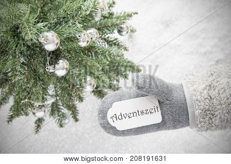 Glove With Label With German Text Adventszeit Means Advent Season. Green Christmas Tree With Silver Balls On Snow In Background. Seasonal Greeting Card With Snowflakes.