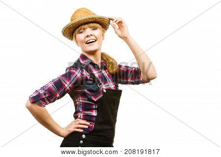 Gardening concept. Attractive woman in dungarees pink check shirt and sun hat posing and smiling. Isolated background