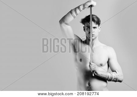 Fitness And Diet Concept. Guy With Flexible Rulers On Purple