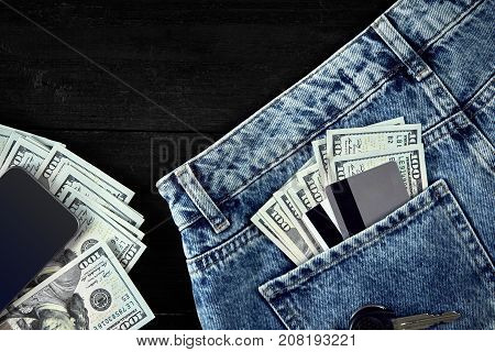 Dollars and cards in your pocket jeans, cash, smart on black wooden background. Top view. Copy space. Still life. Flat lay