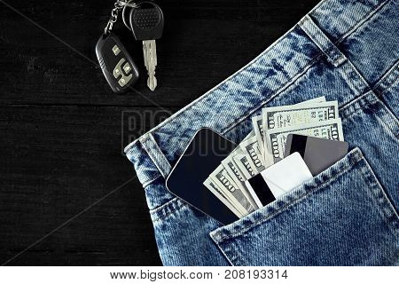 Money, Debit card and Credit card are in pocket of blue jean, Car keys, Smart on wooden background with copy space. One hundred dollar bills and cards in back of jean pocket in concept of business