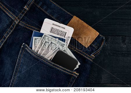 Dollars, smart, passport and plane ticket in your pocket jeans on black wooden background. Top view. Copy space. Still life. Flat lay