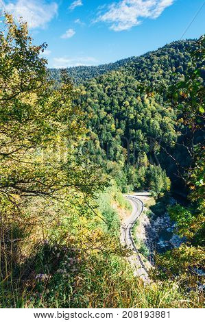 Sunny autumn landscape with road and river in the foothills of Adygea top view