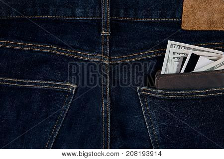 Money, Debit card and Credit card are in pocket of blue jean on wooden background with copy space. One hundred dollar bills and cards in back of jean pocket in concept of business and finance.