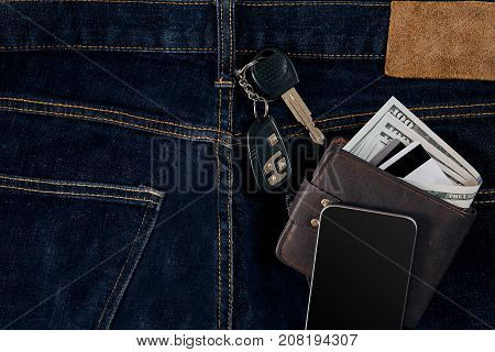 Money, Debit card and Credit card are in pocket of blue jean, Car keys, Smart. One hundred dollar bills and cards in back of jean pocket in concept of business and finance.
